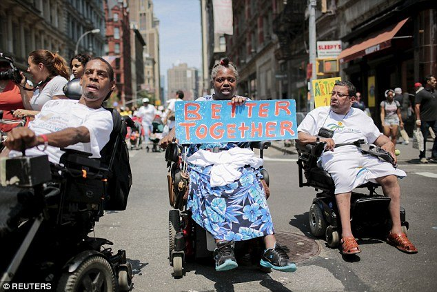 Three people in wheelchairs marching in the NYC Disability Pride Parade. One holding a sign saying 'Better Together'