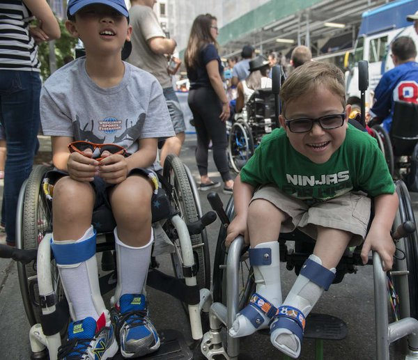 an image of 2 kids in a wheelchair smiling in the Disability Pride Parade
