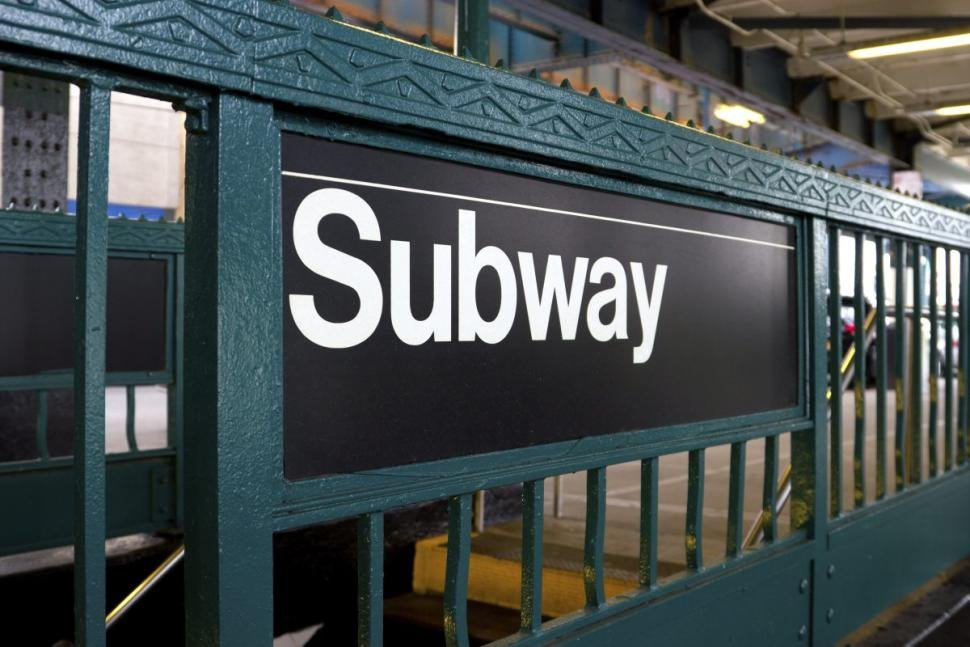An image of a subway sign on the side of entrance