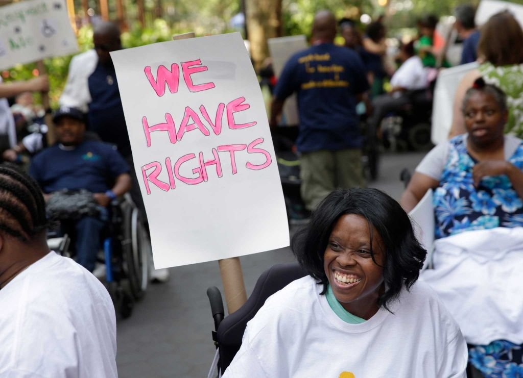 """A group of people holding a sign saying """"We have rights"""""""