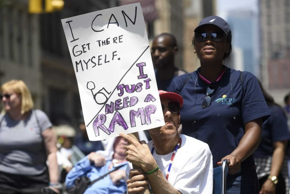 "A participant holds a sign saying ""I can get there myself, I just need a ramp."""