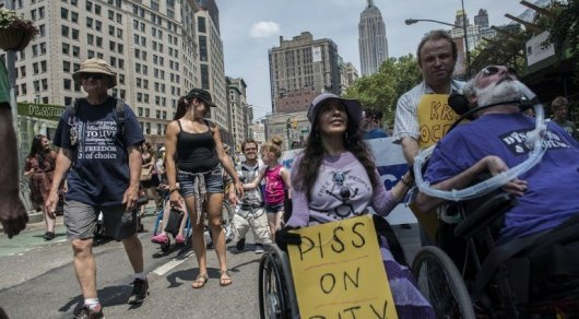 People participate in the first annual Disability Pride Parade. Two wheelchair users in front and dozens of people marching behind.