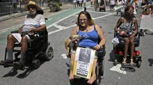 Jessica Delarosa, and her dog Mayim, and two other wheelchair marchers participate in the inaugural Disability Pride Parade